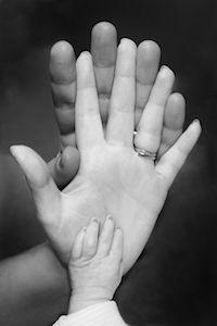 Baby Hand mit Händen vom Mann und Frau